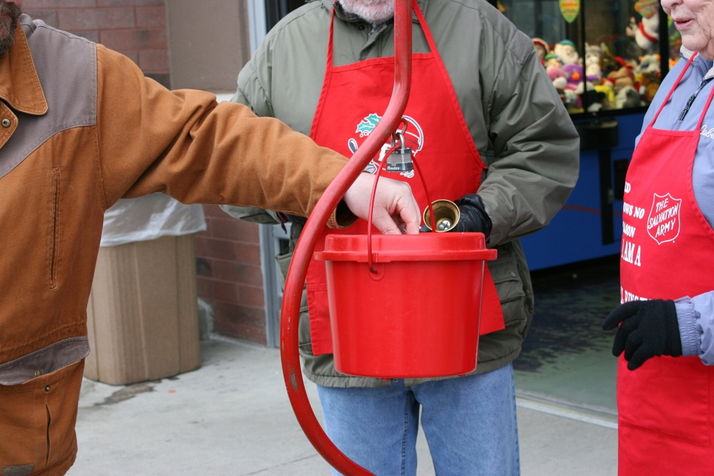 A man drops coins into the red kettle tended by Bud and Bev.