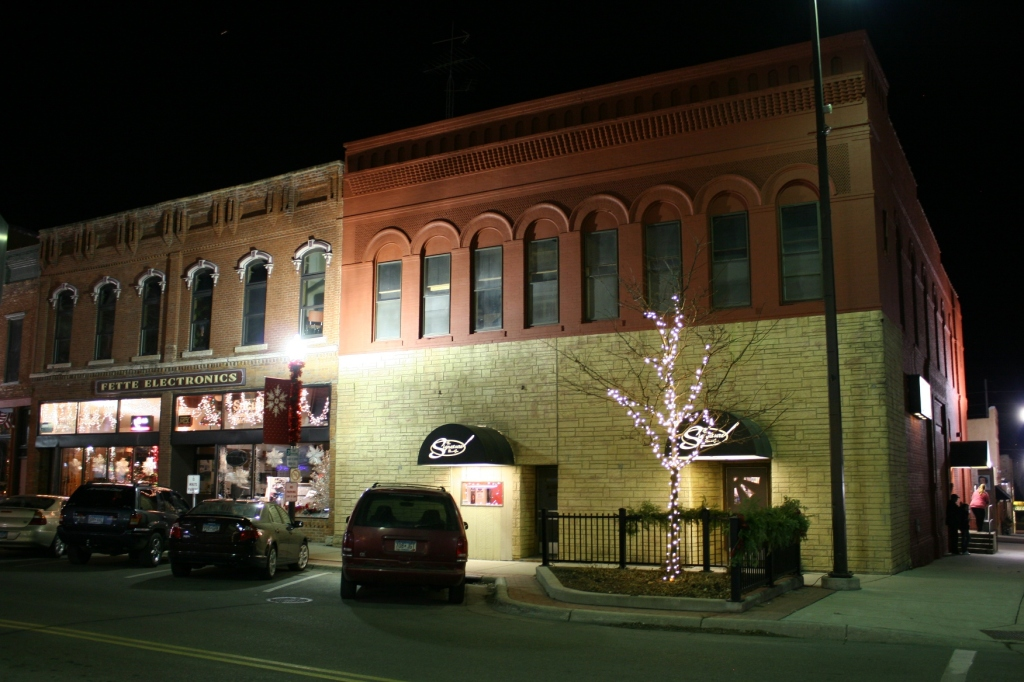 """Lights adorn trees in the downtown including next to the Signature Bar & Grill, Faribault's version of """"Cheers."""" Here you'll find, in my opinion, the best pizza in town."""