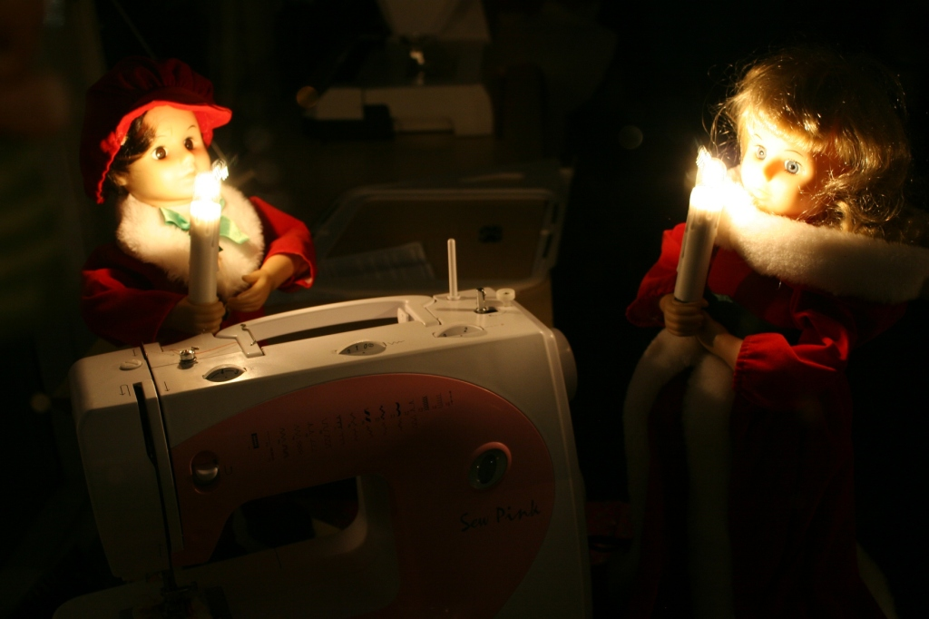 Festively dressed dolls snug at sewing machine at B & J Sewing Center.