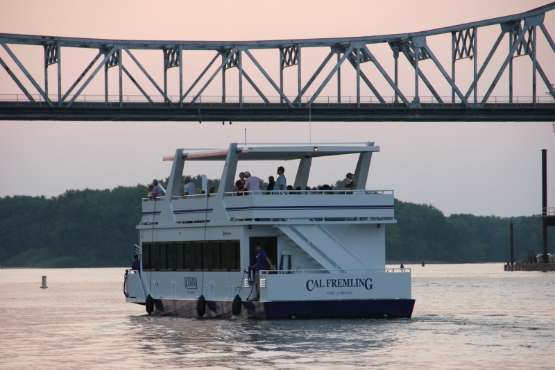 As the sun sets, Winona State University's Cal Fremling boat passes under the Mississippi Rover bridge in Winona. Minnesota Prairie Roots photo, September 2015.