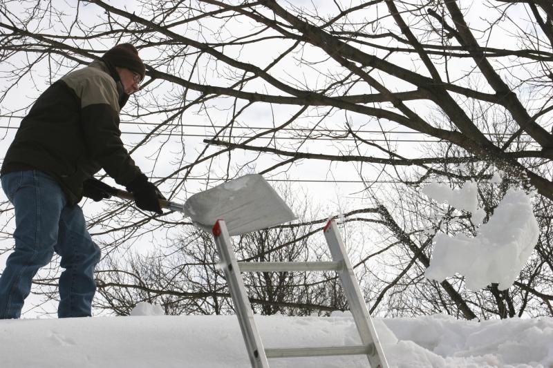 Shoveling snow off roof, 69
