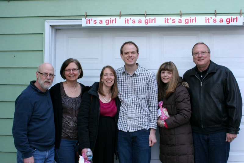 The grandparents-to-be flank the parents-to-be. From left to right, my husband, me, Amber, Marc and Marc's parents, Lynn and Eric. We are standing outside the garage door where I hung the banner. I found the banner packed in a shoebox. Next-door-neighbors hung the banner on our garage door 28 years ago when our youngest daughter, Miranda, was born.