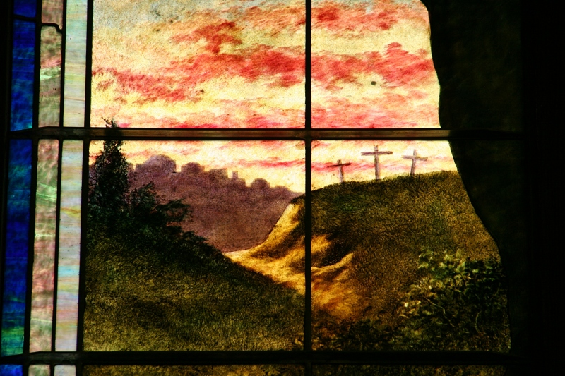 Look at the details of three distant crosses in this snippet of a stained glass window.