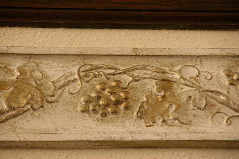 Grapes carved into wood along the balcony.