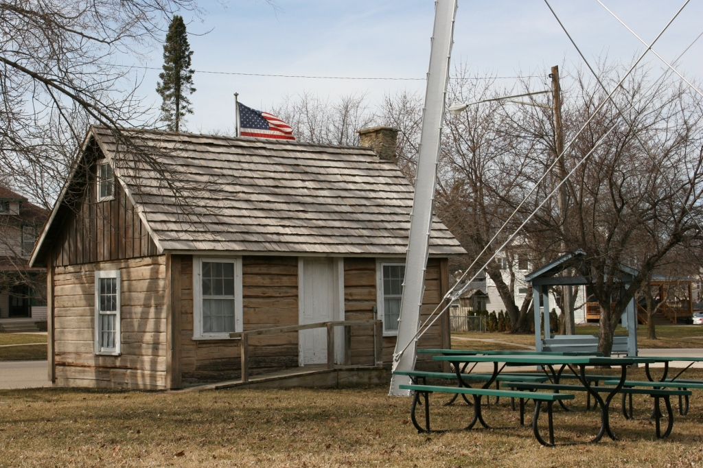 The Lars Larson log cabin sits next to the water tower in Wanamingo. The information center can be seen to the right