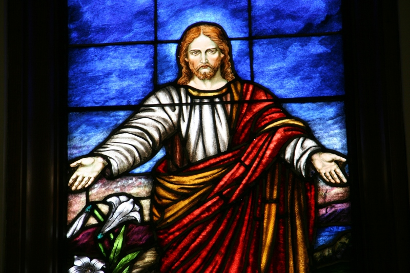 The risen Lord centers the trio of stained glass windows above the altar.