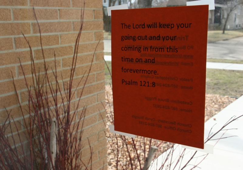A final message for worshipers is posted on a window next to an exterior front door.