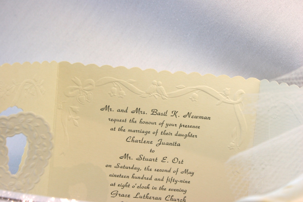 The invitation to the wedding of Charlene Newman and Stuart Ost is displayed in a case.