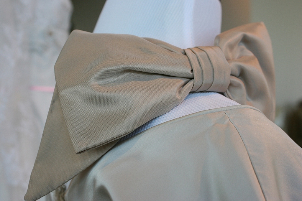 This bow sits on the shoulder/neckline of a dress.