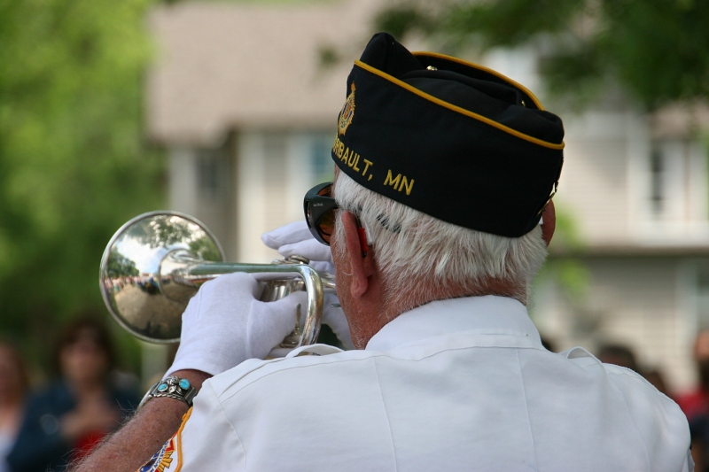 A veteran plays taps at the conclusion of the program.
