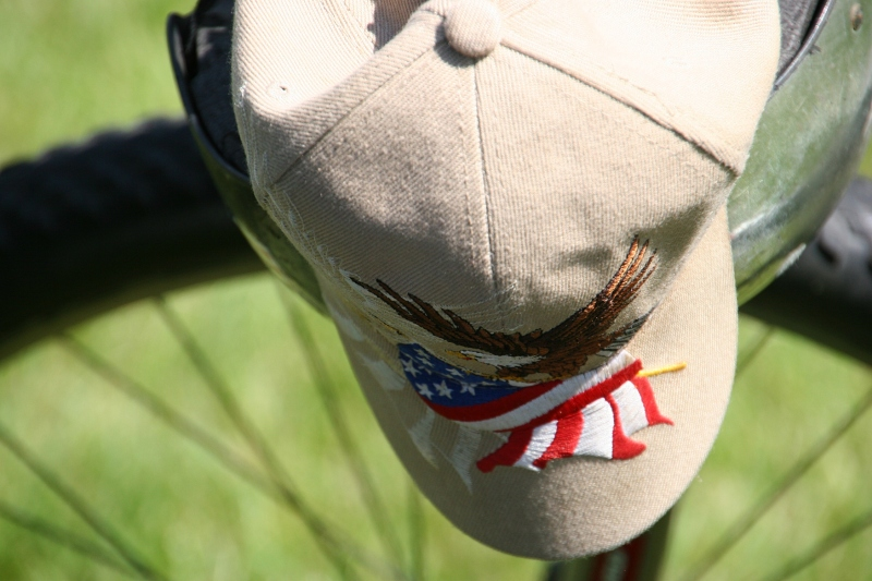 A patriotic cap hangs from a bicycle.