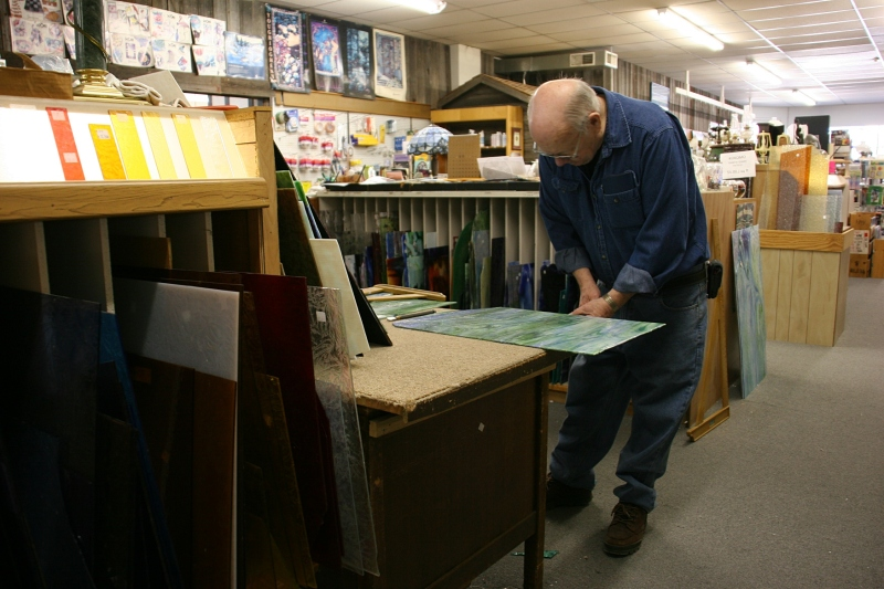 Mike cuts salvaged stained glass to sell.