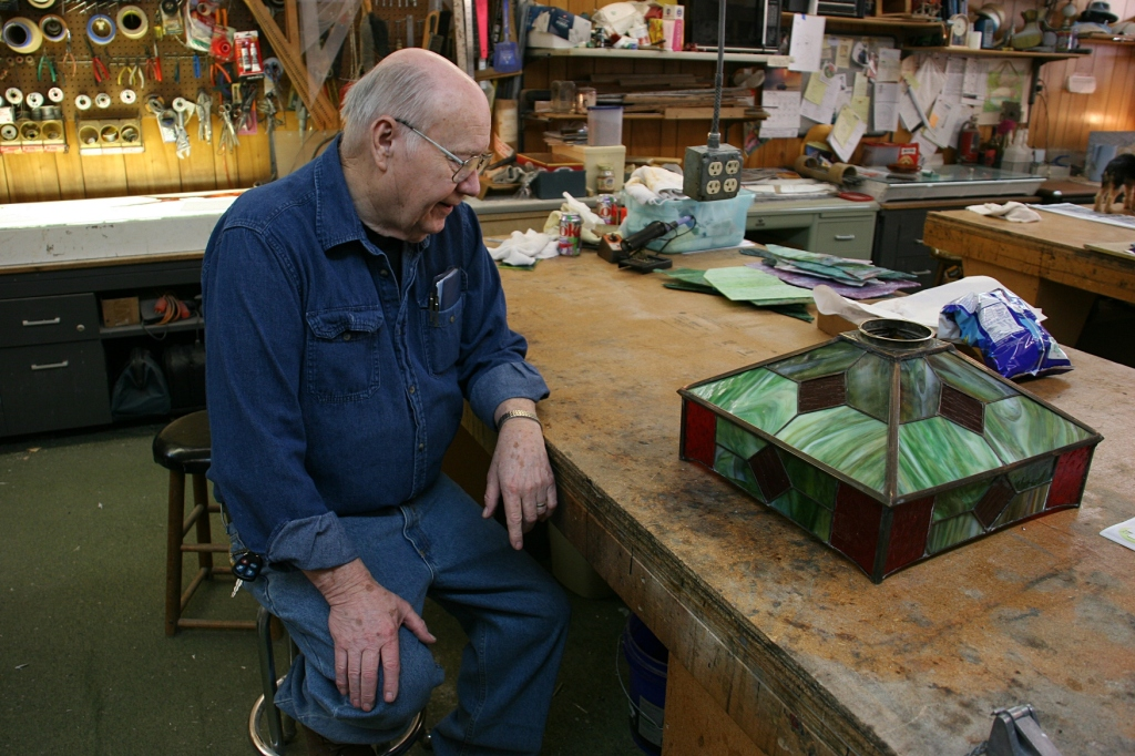 In his workshop, Mike talks to customers who've stopped by to pick up their restored light shade.