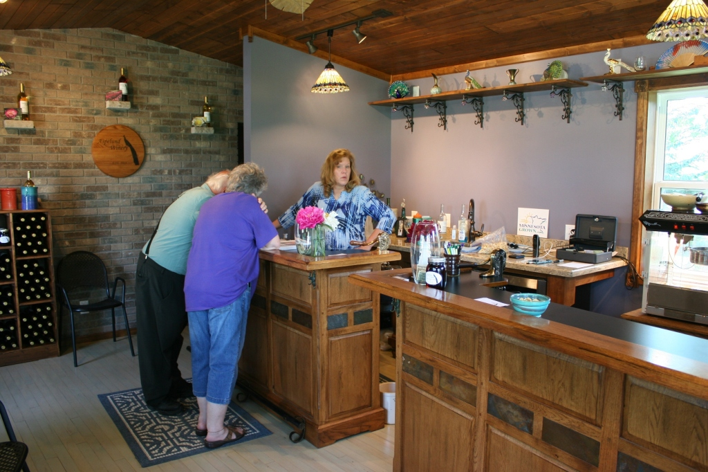 Dawn meets with customers who are perusing a peony catalog in the wine tasting room.