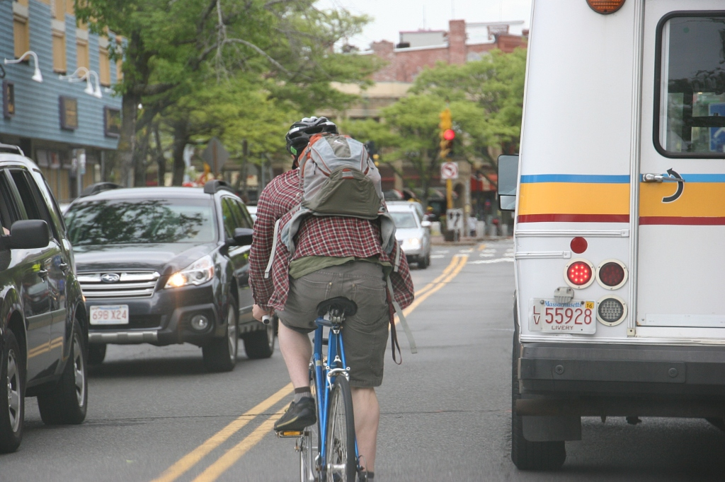 A biker squeezes around a bus in busy Davis Square.