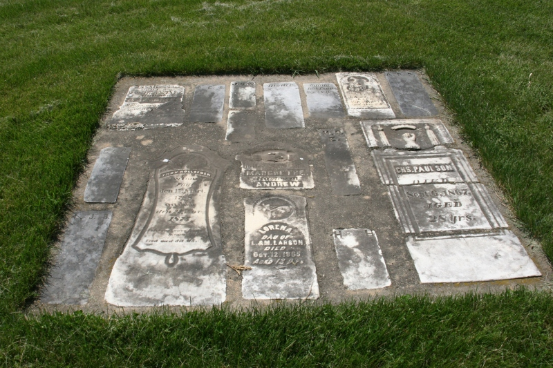 Aged tombstones, which I assume once stood vertically, are now cemented flat into the ground.