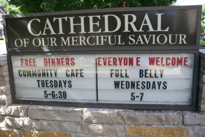 A sign in front of the church advertises the free meals served here twice a week.