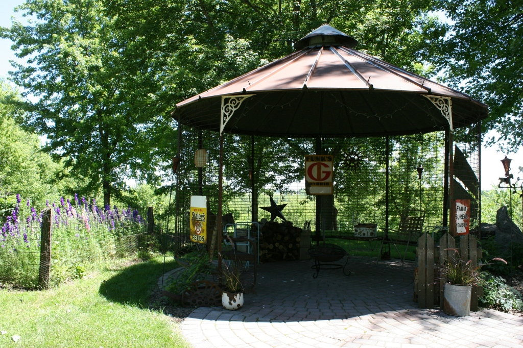 Farm themed decor fits this corn crib turned fire pit gathering area.