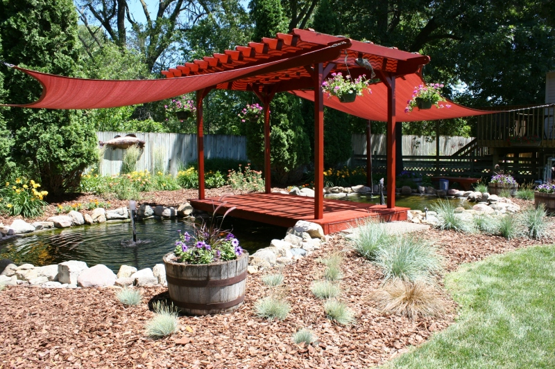 Pond, pergola and bridge create a focal point in the yard.
