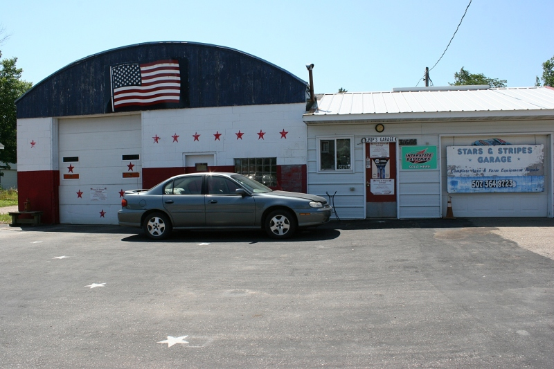 The Stars & Stripes Garage in Heidelberg, Minnesota, photographed several weeks ago. Normally I would crop the parking lot section of the image. But it's an important part of the scene with white stars painted upon asphalt.