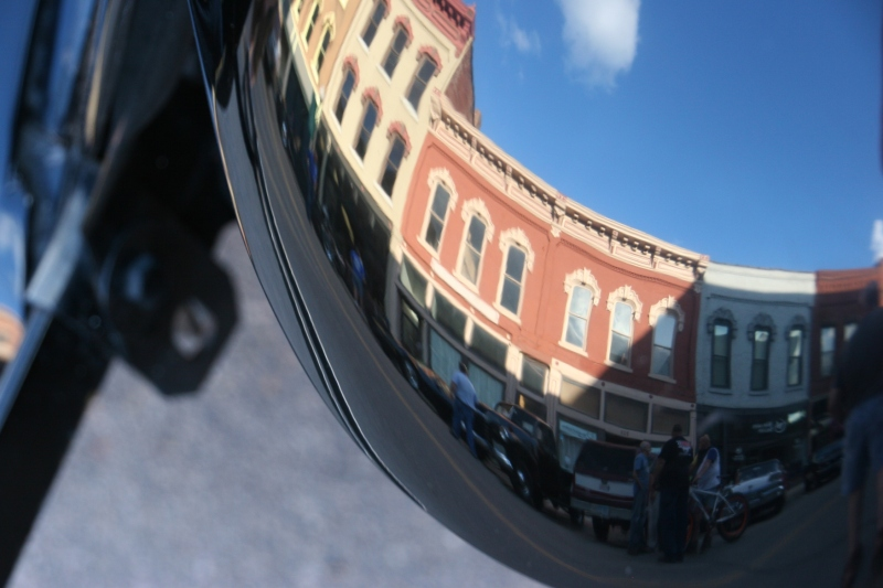 Historic buildings reflected in a polished vehicle at Car Cruise Night.
