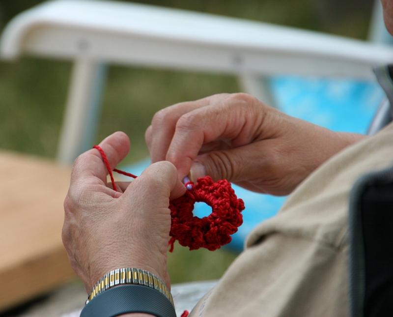 A fest goer crochets while musicians perform.