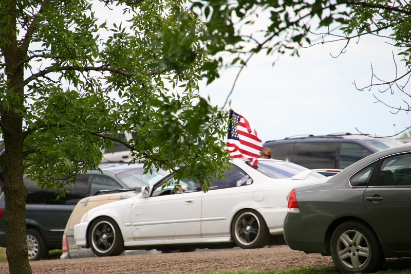 A flag bedecked car passes the festival grounds.