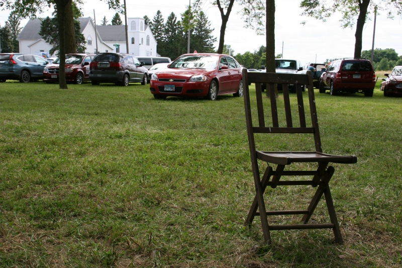 A fest-goer left this vintage wooden folding chair sitting behind the ice cream stand. In the background you can see Trinity Lutheran Church and School across the road.