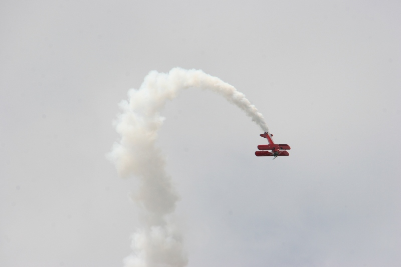 A biplane buzzes the festival grounds mid-afternoon.