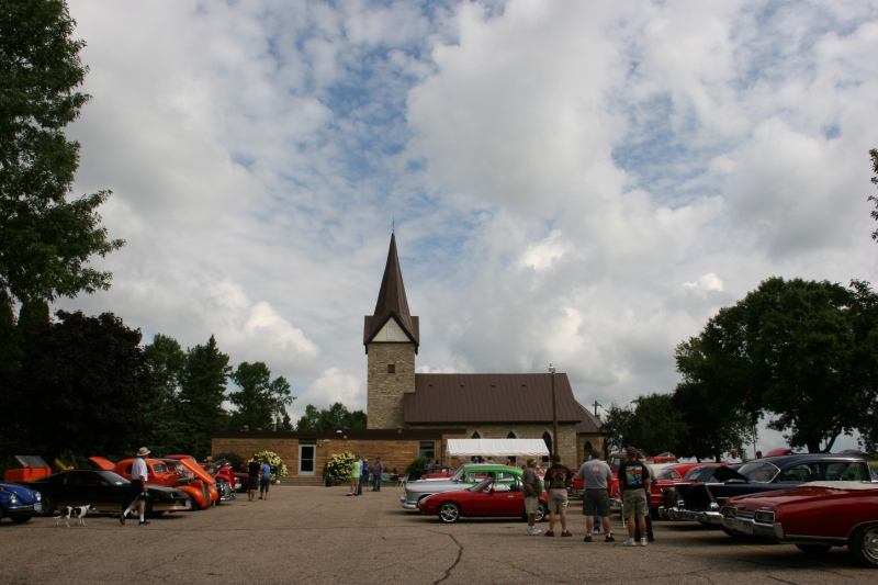 An overview of the car show next to the church.