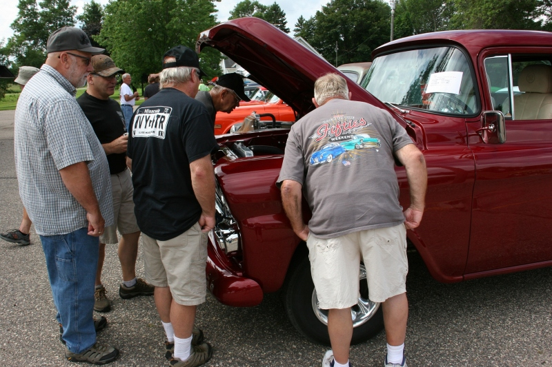 This group of men visited for a long time around various vehicles.