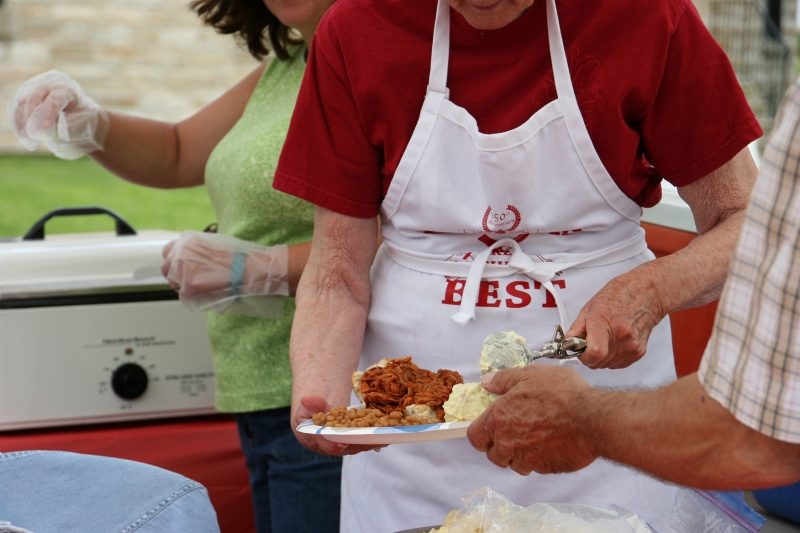 Volunteers served up a generous plate of a BBQ pulled pork sandwich, potato salad and beans, all for $5.