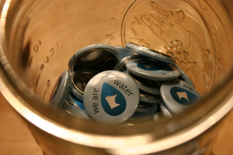 """We Are Water MN"" pins in a jar at the exhibit."