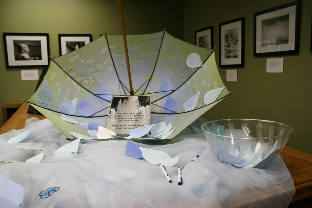 """In a side room, you'll find Kay Herbst Helms' photo exhibit, """"Water Rights?"""" In the table display, visitors are asked to pen their thoughts on water."""