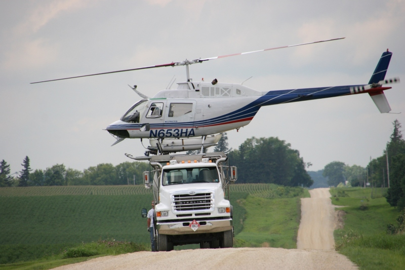 Helicopter spraying, 124 atop mixing truck