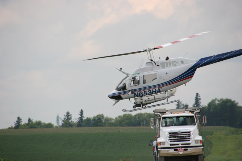 The helicopter lifts off from the mixing truck, ready for another round of spraying.