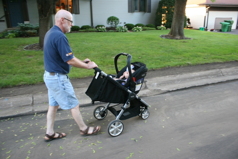 Grandpa pushes his little girl during an evening walk.
