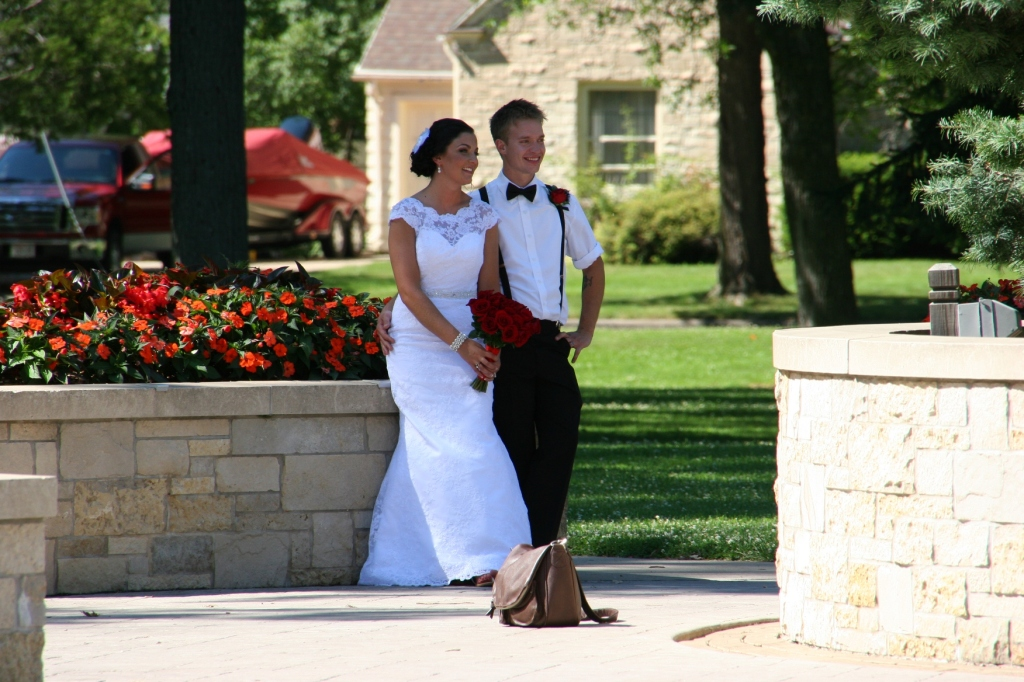 """""""Ring Dance"""" seems fitting for a wedding photo shoot. Here the couple poses near a massive round flowerbed in City Park."""