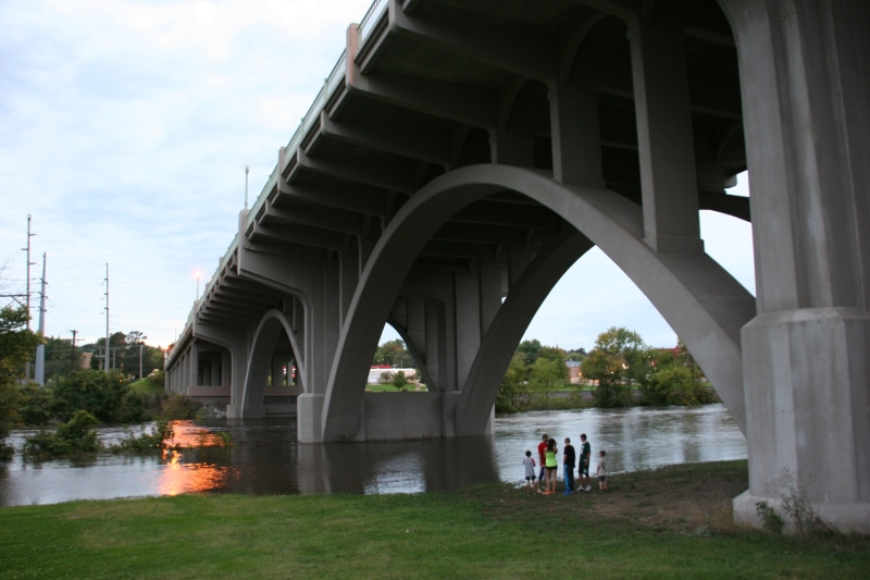 Locals are drawn under the viaduct that links the west and east side of Faribault during yet another flood in our community caused by excessive rainfall. Here the Straight River runs