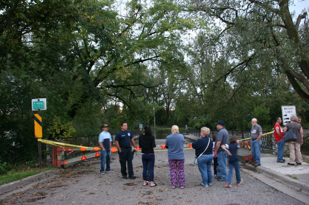 Onlookers gather at the bridge entry to Teepee Tonka Park, now flooded by the Straight River.