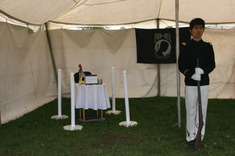 Inside a tent reserved for remembering those missing in action and those who were prisoners of war, a member of the Shattuck-St. Mary's School Crack Squad stands at rigid attention.
