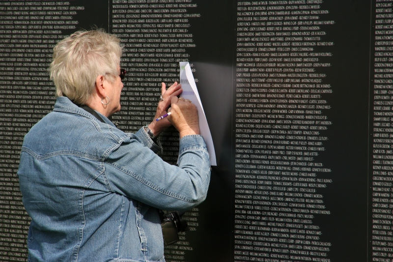 A woman does rubbings of names on the wall.