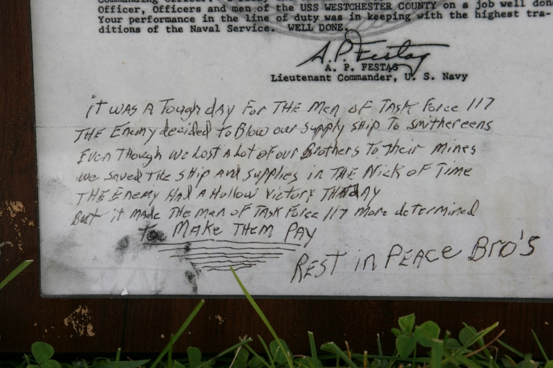 A framed letter of commendation with a soldier's notes was left at the wall.