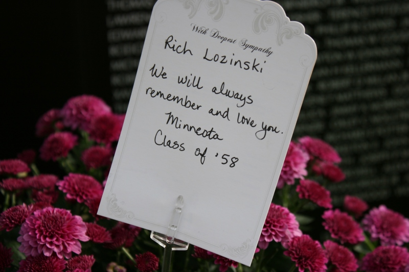 Grief in a note and mums left at the wall in honor of Rich Lozinski, Class of 1958, Minneota, Minnesota.