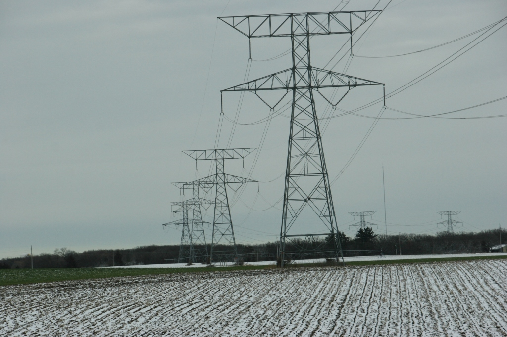 Under grey skies on the flat land north of Monticello, snow dusts fields.