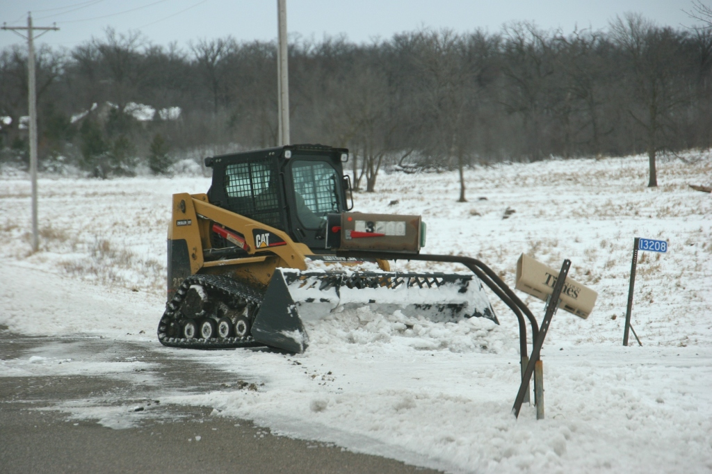 A rural resident cleans out the end of his driveway along Benton County Road 3.