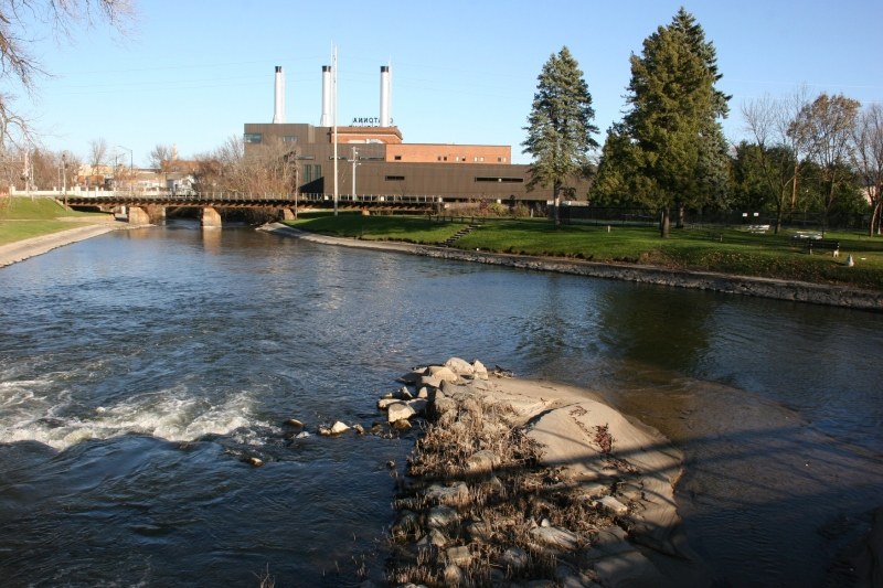 The Straight River flows toward the historic Owatonna Public Utilities building.
