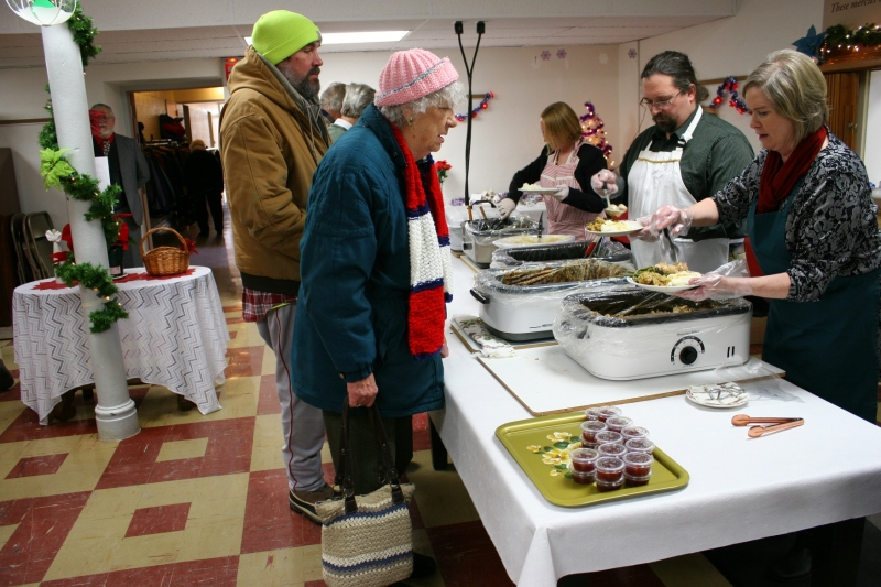 Volunteers plate a meal of turkey, mashed potatoes and gravy, stuffing, meatballs and green beans for diners. Additionally, cranberries and Christmas Cake were on the menu.
