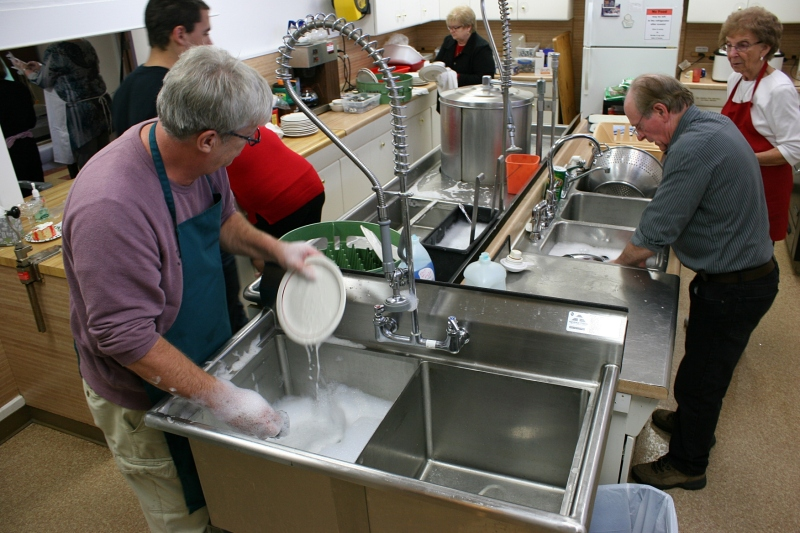 Behind the scenes, volunteers are busy washing dishes.