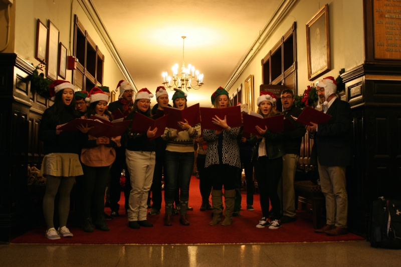 In the Shumway Hall entry hall, carolers sing for Christmas Walk guests.